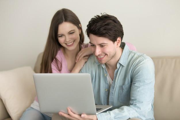 Junges glückliches paar, das unter verwendung der laptop-computers sitzt Kostenlose Fotos