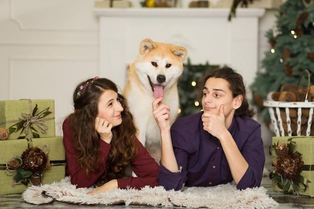 Junges glückliches paar, das zu hause entzückenden hund akitas inu mit auf dem boden für weihnachtsfeiertage streichelt. Premium Fotos