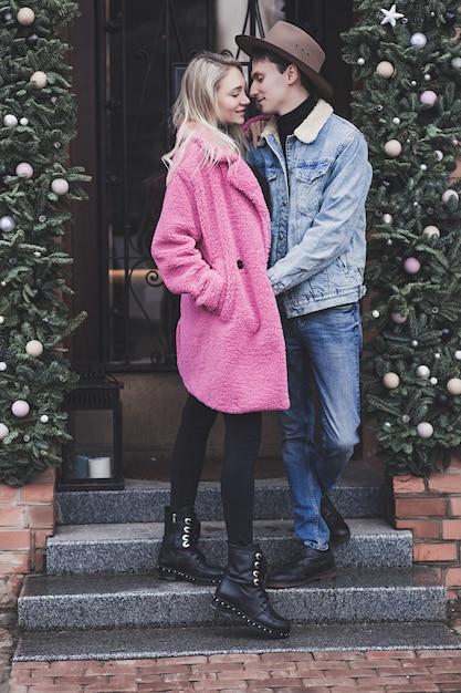 Junges glückliches paar in der liebe, die im treppenstraßencafé umarmt Premium Fotos