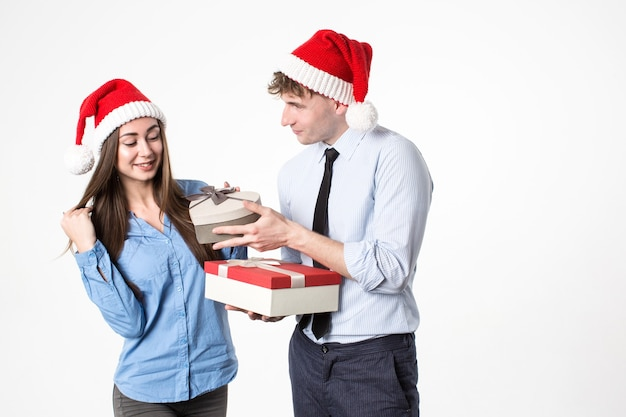 Junges glückliches paar in der weihnachtsmannmütze mit geschenkboxen Premium Fotos