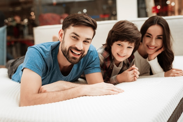 Junges glückliches paar und little boy auf bett im speicher Premium Fotos
