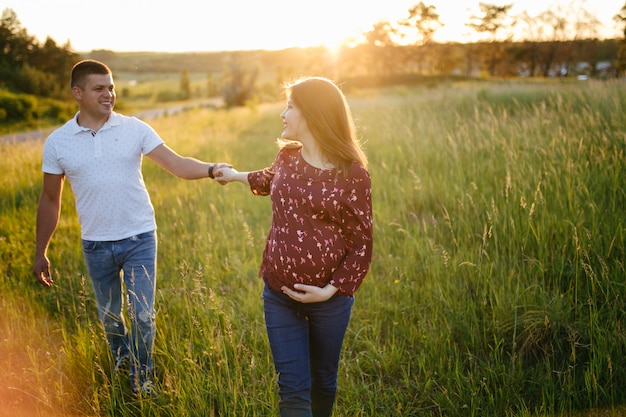 Junges glückliches schönes paar in der liebe, die zusammen auf gras- und baumparklandschaft geht Kostenlose Fotos