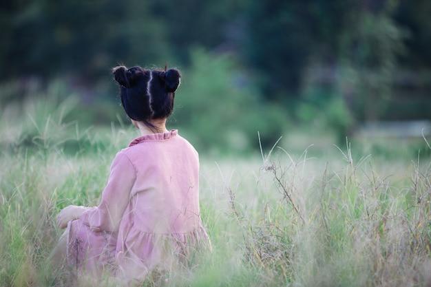 Junges hippiemädchen, das auf einem gebiet sitzt. Kostenlose Fotos
