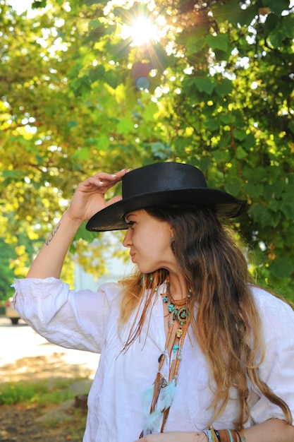 Junges hipsterartfrauenporträt im stadtpark, sonniger tag, schwarzer lederhut Premium Fotos