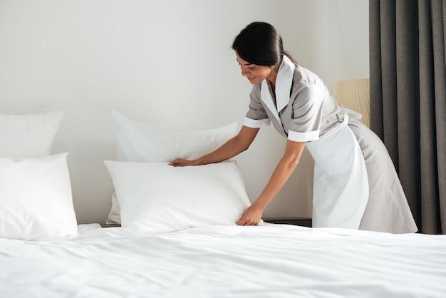 Junges hotelmädchen, das kissen auf bett aufstellt Kostenlose Fotos