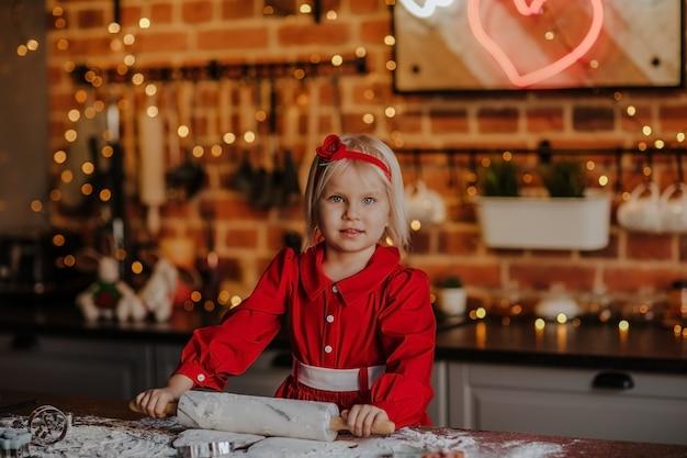 Junges hübsches blondes mädchen im roten winterkleid, das an der küche mit weihnachtshintergrund kocht Premium Fotos