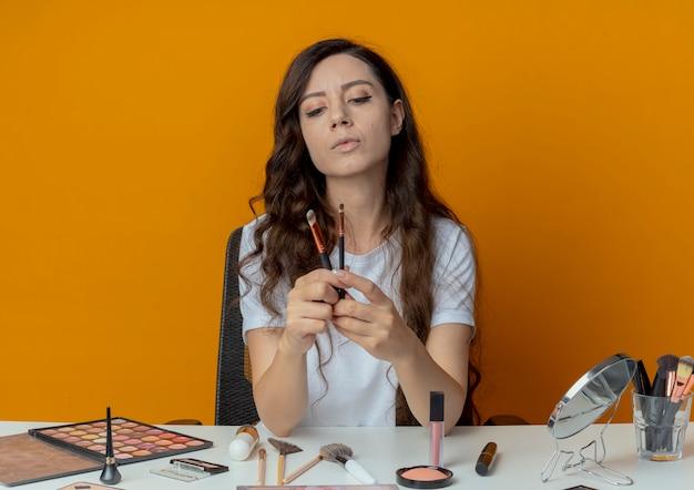 Junges hübsches mädchen, das am make-up-tisch mit make-up-werkzeugen sitzt und concealer- und lidschattenpinsel lokalisiert auf orange hintergrund hält Kostenlose Fotos
