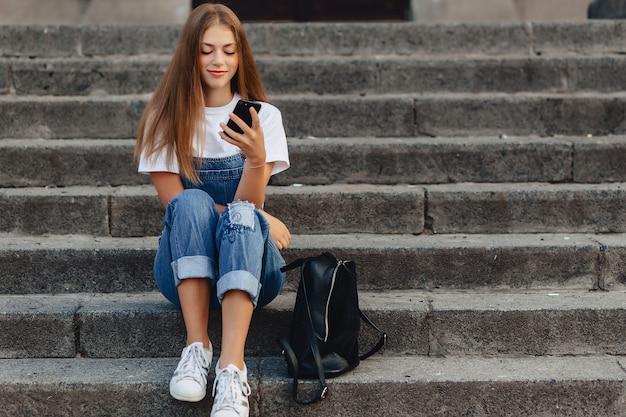 Junges hübsches mädchen mit dem aktenkoffer, der auf treppe sitzt und sms am telefon schreibt Premium Fotos