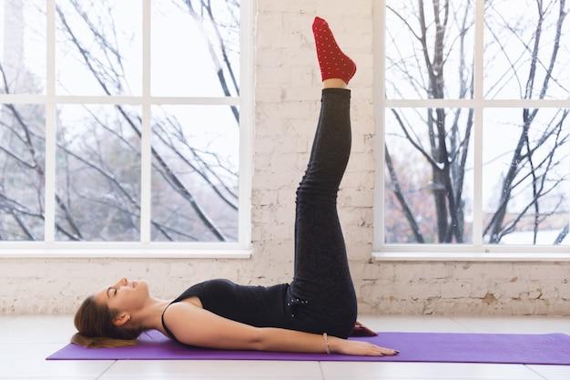 Junges hübsches sportliches yogamädchen liegen auf dem boden mit den beinen oben Premium Fotos