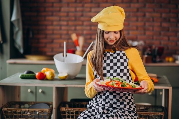 Junges jugendlich mädchen, das salat für frühstück in der küche vorbereitet Kostenlose Fotos