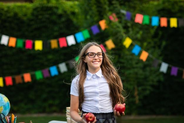 Junges jugendlich mädchen in den gläsern am weißen hemd, das rote äpfel hält Premium Fotos