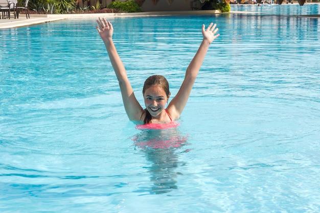 Junges jugendlich mädchen schwimmt und hat spaß im außenpool Premium Fotos