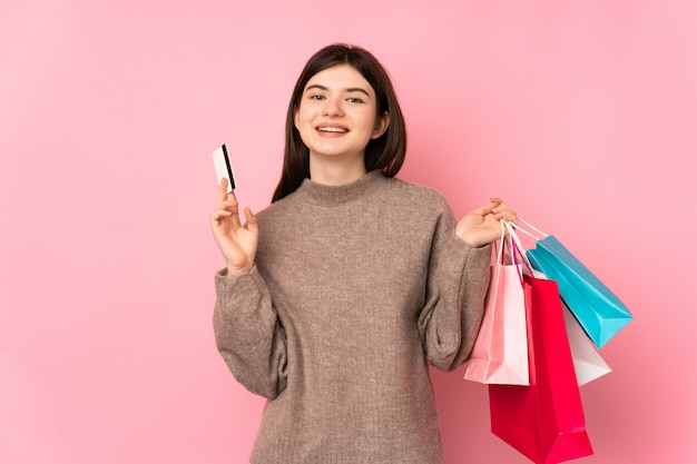 Junges jugendlichmädchen über der rosa wand, die einkaufstaschen und eine kreditkarte hält Premium Fotos