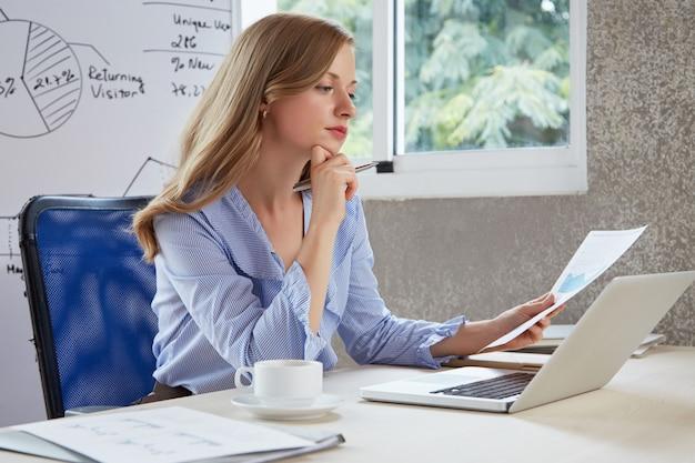 Junges karrieremädchen im büro denkend über dem analysediagramm Kostenlose Fotos