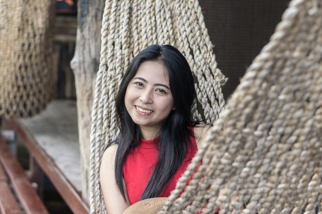 Junges kaukasisches asiatisches mädchen, das in einer hängematte in einer angenehmen faulheit eines wochenendes eveni schwingt Premium Fotos