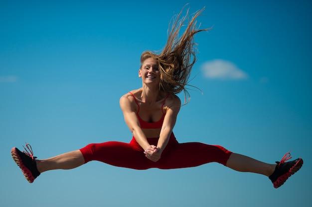 Junges kaukasisches mädchen führt die schnur durch, die auf himmel backround springt, Premium Fotos