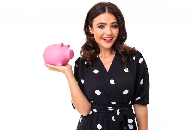 Junges kaukasisches mädchen mit herrlichem lächeln, im schwarzweiss-kleid in den erbsen hält eine rosa schwein moneybox, das bild, das auf weiß lokalisiert wird Premium Fotos