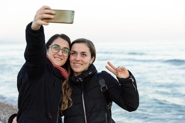 Junges kaukasisches mädchen zwei, das zusammen ein selfie auf dem strand im winter macht Premium Fotos
