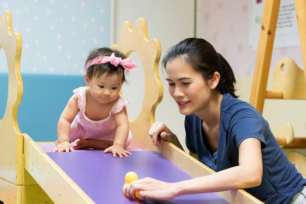 Junges kleines asiatisches baby, das in der turnhalle mit ihrer mutter spielt Premium Fotos