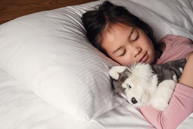 Junges kleines asiatisches mädchen der gemischten rasse, das im bett mit ihrem hundespielzeug, schlafenszeitroutine, weckkind für schule, kinderschlafstörung schläft Premium Fotos