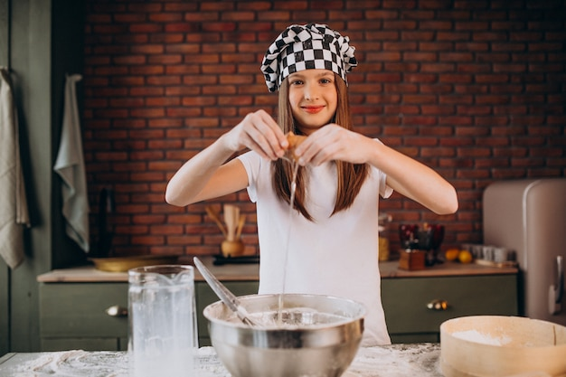 Junges kleines mädchen, das gebäck an der küche zum frühstück backt Kostenlose Fotos