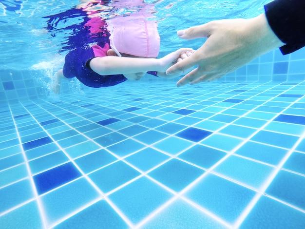 Junges kleines nettes unterwassermädchen schwimmt im swimmingpool mit ihrem schwimmlehrer Premium Fotos