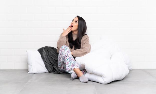 Junges kolumbianisches mädchen in den pyjamas am zuhause gähnenden und weit offenen mund des cings mit der hand Premium Fotos