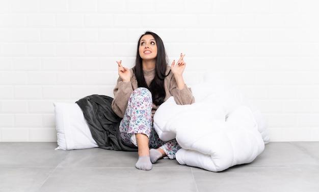 Junges kolumbianisches mädchen in den pyjamas an zuhause mit den fingern, die das beste kreuzen und wünschen Premium Fotos