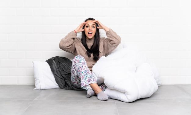Junges kolumbianisches mädchen in den pyjamas an zuhause mit überraschungsausdruck Premium Fotos