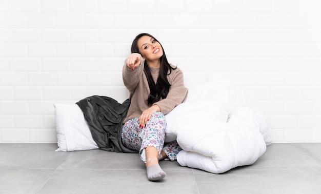 Junges kolumbianisches mädchen in den pyjamas zuhause zeigt finger auf sie mit einem überzeugten ausdruck Premium Fotos