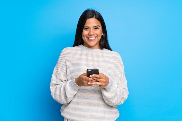 Junges kolumbianisches mädchen mit der strickjacke, die eine mitteilung mit dem mobile sendet Premium Fotos