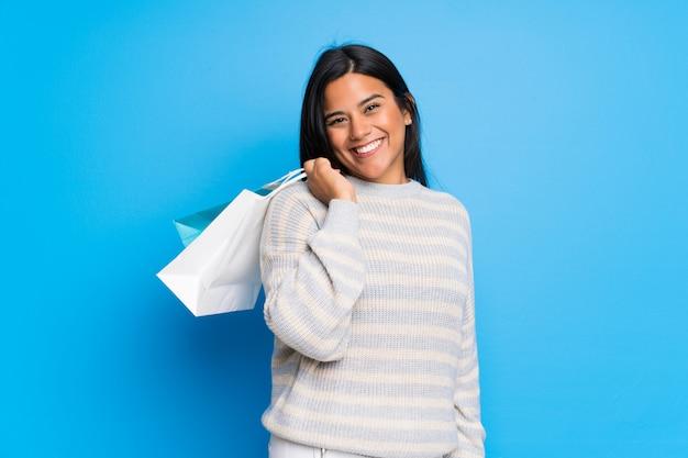 Junges kolumbianisches mädchen mit der strickjacke, die viele einkaufstaschen hält Premium Fotos