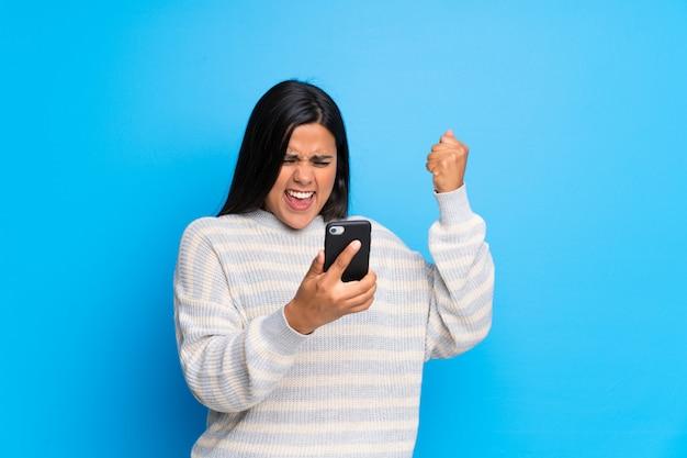 Junges kolumbianisches mädchen mit strickjacke einen sieg mit einem mobile feiernd Premium Fotos