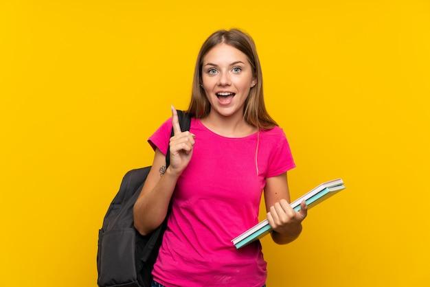 Junges kursteilnehmermädchen über getrennter gelber wand eine großartige idee oben zeigend Premium Fotos