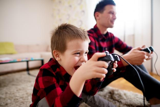 Junges lächelndes kind plant, wie man seinen vater im konsolenspiel besiegt, während man ein gamepad hält und auf dem boden sitzt. Premium Fotos