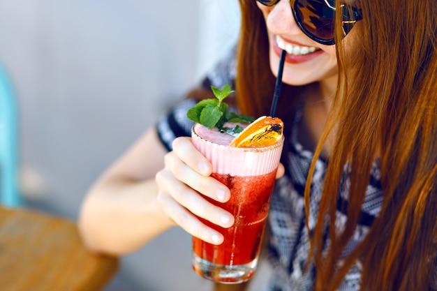 Junges lächelndes mädchen, das leckeren süßen cocktail, erstaunlichen entspannenden tag, leckere limonade, elegantes kleid und sonnenbrille, außenterrasse trinkt. Kostenlose Fotos