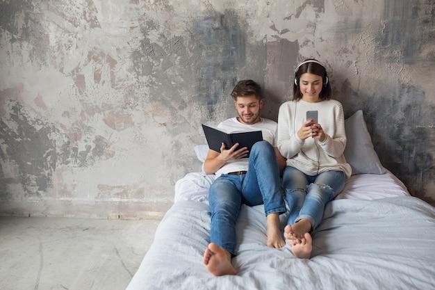 Junges lächelndes paar, das auf dem bett zu hause im lässigen outfit-lesebuch sitzt, das jeans trägt, mann liest buch, frau, die musik auf kopfhörern hört, romantische zeit zusammen verbringend Kostenlose Fotos