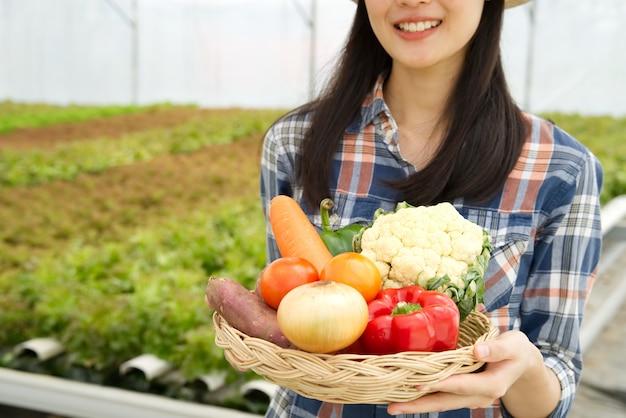 Junges landwirtmädchen, das verschiedenes des gemüses im korb mit lächeln hält Premium Fotos