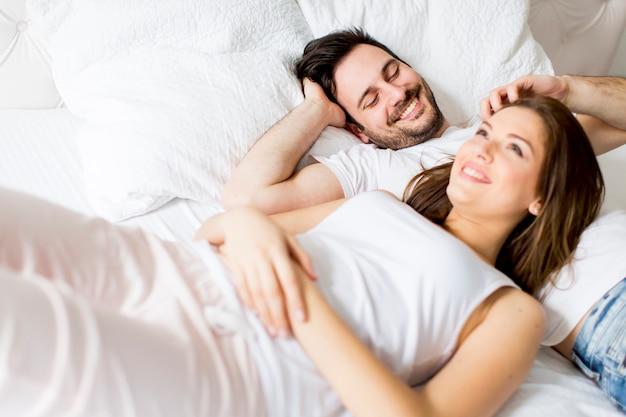 Junges liebespaar im bett Premium Fotos