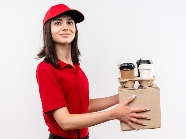 Junges liefermädchen, das rote uniform- und kappenhalteboxpaket und kaffeetassen trägt, die kamera mit lächeln auf gesicht stehen über weißem hintergrund betrachten Kostenlose Fotos