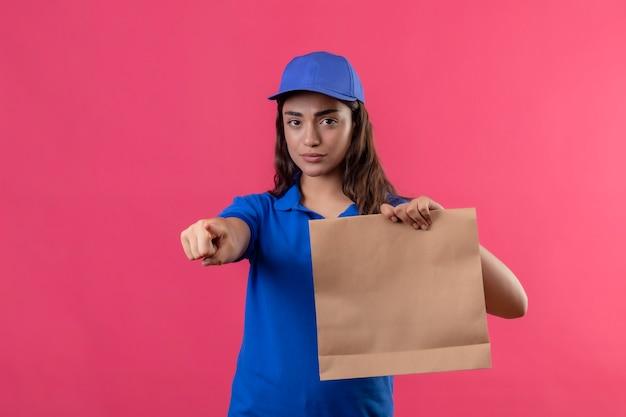 Junges liefermädchen in der blauen uniform und in der kappe, die papierpaket hält, zeigt mit dem finger zur kamera unzufrieden, die über rosa hintergrund steht Kostenlose Fotos
