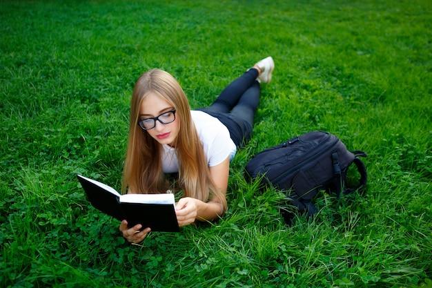 Junges mädchen, das auf dem gras im park liegt, buch studiert oder hausarbeit tut Premium Fotos