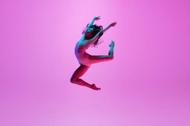 Junges mädchen, das auf rosa wand springt Kostenlose Fotos