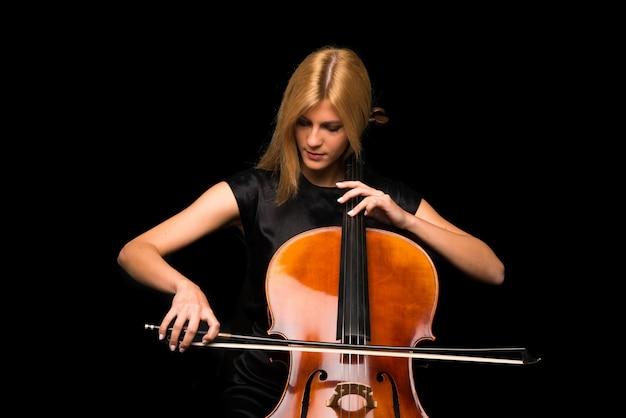 Junges mädchen, das das cello auf lokalisiertem schwarzem hintergrund spielt Premium Fotos
