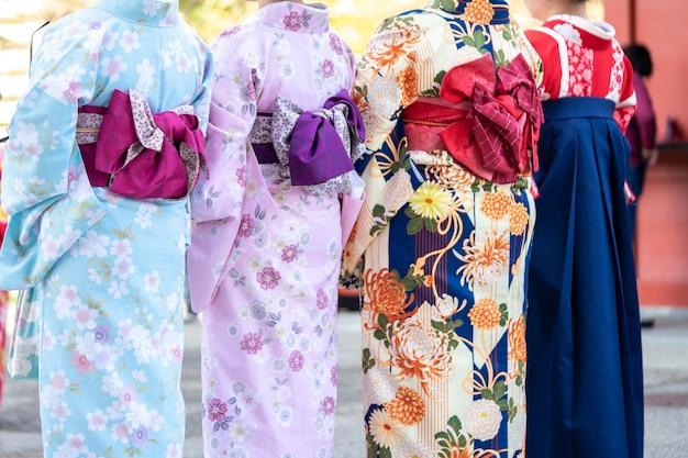 Junges mädchen, das den japanischen kimono steht vor sensoji-tempel trägt Premium Fotos