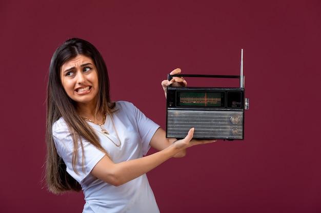 Junges mädchen, das ein altes radio in der hand hält und durch die lautstärke gestört wird. Kostenlose Fotos