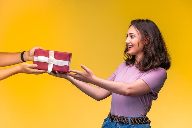 Junges mädchen, das eine geschenkbox von ihrem freund an ihrem jahrestag nimmt Kostenlose Fotos
