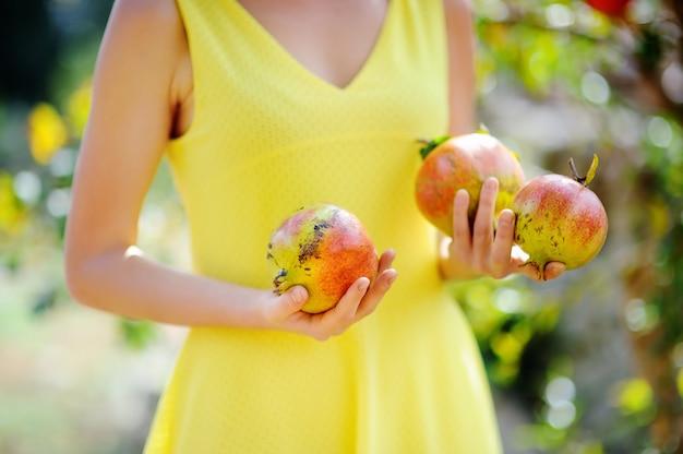 Junges mädchen, das frische reife granatäpfel im sonnigen garten in italien auswählt. weiblicher landwirt, der im obstgarten arbeitet Premium Fotos