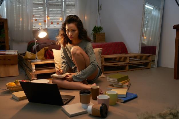 Junges mädchen, das für die prüfung gesetzt auf dem boden ihres schlafsaalraumes umgeben durch laptop, bücher und leere schalen sich vorbereitet Kostenlose Fotos