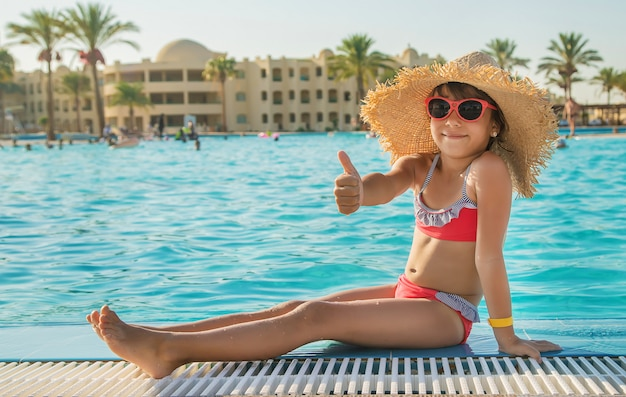 Junges mädchen, das im swimmingpool sich entspannt Premium Fotos